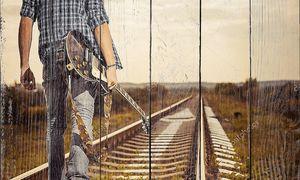 Человек с гитарой на железной дороге