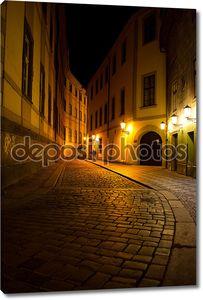 человек, идущий по улице старого города ночью в pragu
