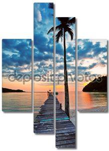 Вид на пляж с пальмами и Пирс на закате