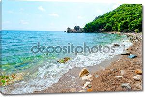Каменистый пляж, зеленый холм, лазурные воды моря