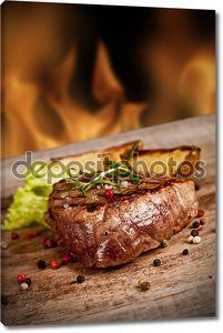 Вкусный стейк на огненном фоне
