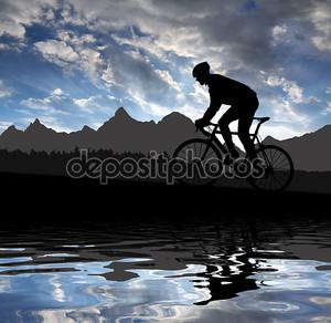 Силуэт велосипедиста на фоне гор