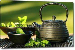 черный азиатский заварной чайник с чаем монетного двора