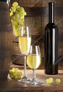два бокала вина, бутылки и бочки