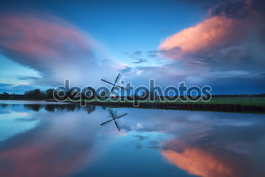 Драматические бурные закат над голландской ветряной мельницы и река
