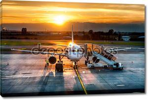 Самолет возле терминал в аэропорту на закате