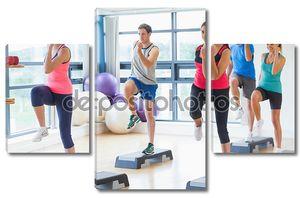Инструктор с фитнес-класс, выполняющего Степ-аэробика упражнения