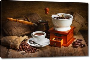 Кофемолка рядом с кружкой эспрессо