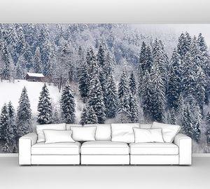 Маленький дом в заснеженном лесу в швейцарских Альпах
