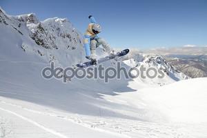 Сноубордист в прыжке на фоне гор