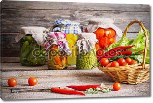консервированные и свежие овощи на деревянный фон
