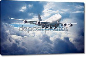 Самолет идет на посадку. Против пасмурное небо