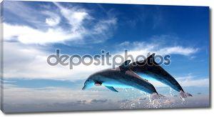 Пара дельфинов прыгать против голубого неба.