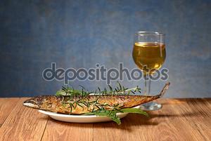 испеченная рыба макрели и вино в стакане