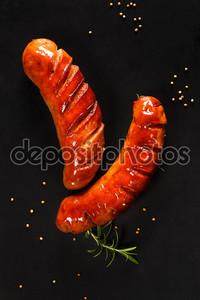 Колбаски гриль на черном фоне