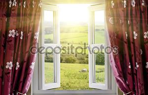 Открытое окно с видом на загородную местность и солнечного света