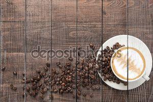 Чашка кофе и кофейные зерна на деревянном фоне