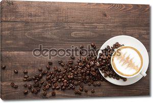 Чашка кофе и кофейных зерен на деревянных фоне. Вид сверху.