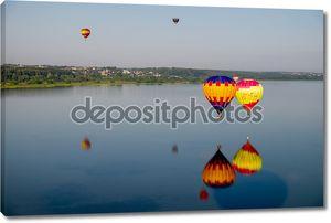 монгольфьеры, пролетающие над озером.