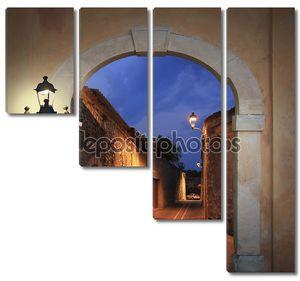 угрюмый освещенная пер с арочными воротами и горящий фонарь