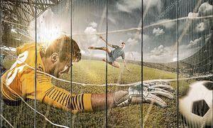 Вратарь в воротах прыгает на ловящий мяч