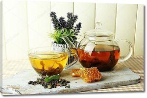 чашка и чайник зеленого чая с медом на столе на фоне деревянных