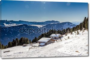 Panorama of the Dolomites with wood cottage, snowy mountains and