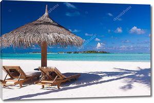 Стулья и зонтик на пляже с тенью от Пальмы