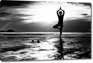 Черно-белые Фото: молодая женщина йогой на пляже на закате.