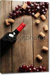 Стеклянная бутылка вина с пробки и виноград на фоне деревянный стол