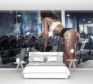 Красивая сексуальная женщина делает тренировки с гантелями