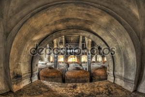 Вид через арку конкретных бродильные чаны в заброшенной