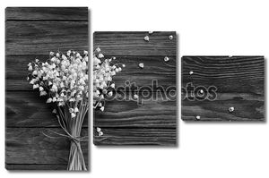 Букет из белых цветов ландыша и упали бутоны на деревянных досках в черно-белом