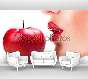 Сексуальная женщина, едящая красное яблоко, чувственные красные губы