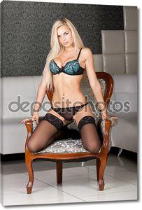 Стильная  блондинка  модель в сексуальном черном белье на стуле Винтаж