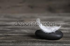 Белое перо на черный камень: идея для соболезнований карты.