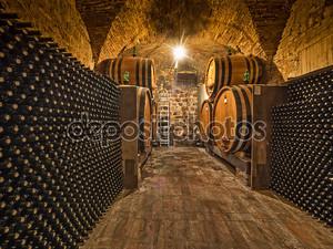 бутылки вина и дубовые бочки в погребе