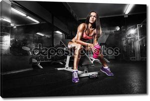 девочка фитнеса с шейкером, позирующим на скамье в спортзале