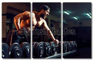 Мускулистые мужчины культурист, тренируясь в тренажерном зале