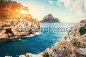 Закат над морем с камнями в Италии. Сицилия
