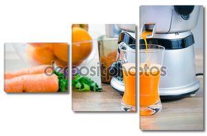 Соковыжималка и морковный сок. фрукты в фоновом режиме