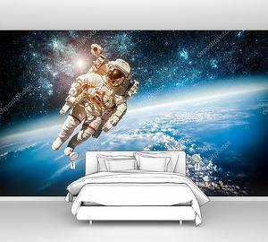 Космонавт в космосе  над Землей