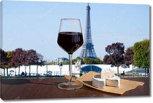 Стакан вина с сыром бри на фоне Эйфелевой башни