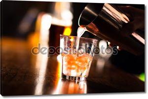 Бармена наливание коктейль в стакан