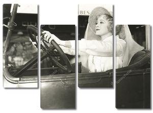 Женщина в огромной шляпе за рулем