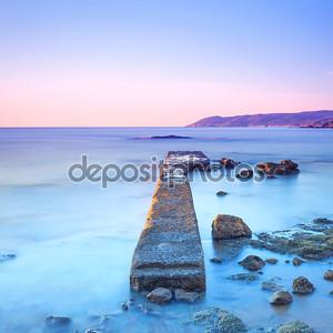 Бетонный мол или причал и скалы на синее море. Холмы на backgro
