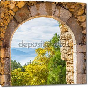 Красивый пейзаж деревьев, гор и моря через старый породы замок Паламиди на город Нафплион в Греции.