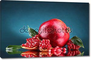 Спелый гранат фрукты с листьями на синем фоне