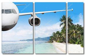 Самолет летит над островом и морем летом на Сейшельских островах
