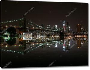 Бруклинский мост ночью отражают в Ист-Ривер и Нью-Йорк на фоне линии горизонта. Башня свободы